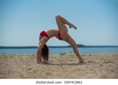 Young Woman Relaxing and Sunbathing At Beach. Beautiful woman in red bikini doing yoga while standing on bridge pose with sea view on background