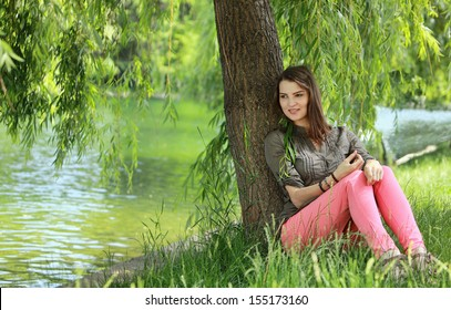 Young woman relaxing under a willow near a pond in a park in summer.