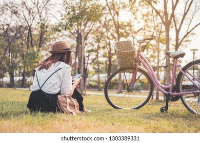 Young woman relaxing and using smart phone and surf internet in the park