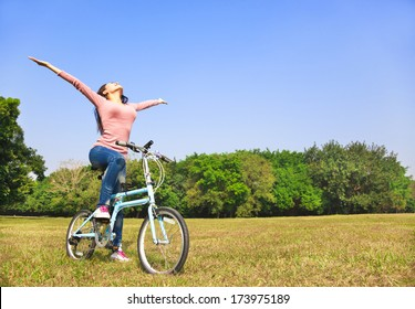 Young woman relaxing while sitting on a bike.