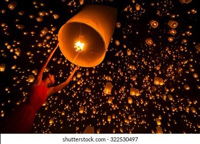 Young woman release sky lanterns to worship buddha's relics in yi peng festival, Chiangmai thailand