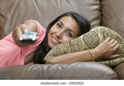 A young woman with remote control relaxing on sofa