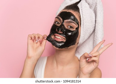 The young woman removed the black mask of her face. isolated on pink background