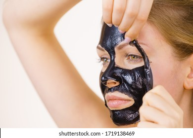 Young woman removing carbo black peel-off mask from her face, on white. Teen girl taking care of oily skin, cleaning the pores. Beauty treatment. Skincare.