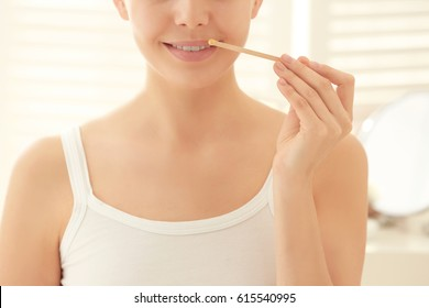 Young woman removing facial hair with wax on blurred background