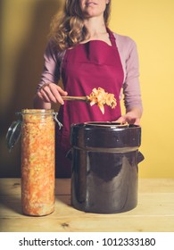 A young woman is removing her delicious and nutritious homemade kimchi from a fermentation pot