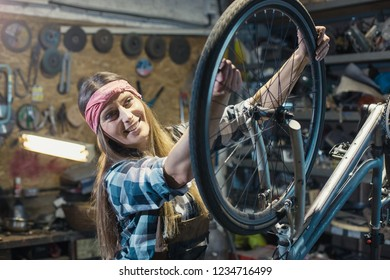 young woman repairing bicycle wheel in a workshop