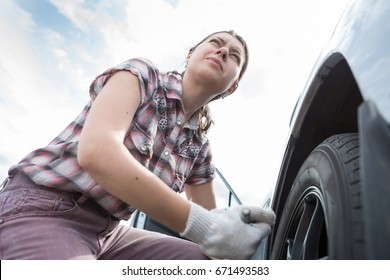 A young woman repairing a car, unscrew and changes the wheel