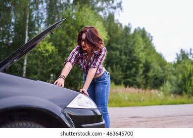Young woman repairing her car