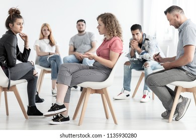 Young woman resolving problem with rebellious friend during group therapy with counselor