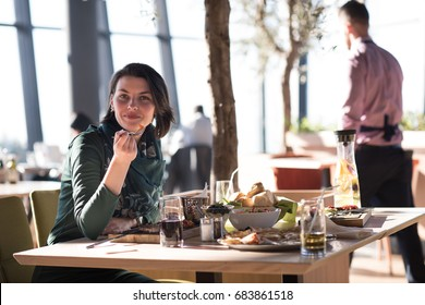 young woman at a restaurant having lunch and looking happy