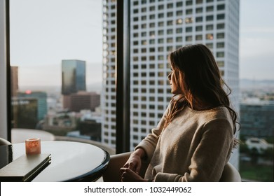 Young woman at restaurant on 35 floor, sitting at table enjoying the city skyline at sunset with stunning panoramic view of Los Angeles.