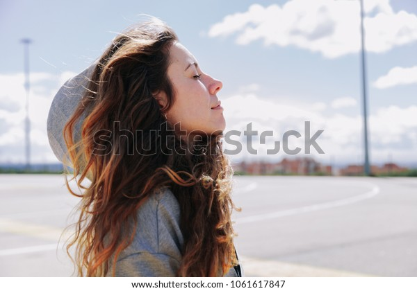 Young woman resting after run wearing a sweatshirt and breathing deeply