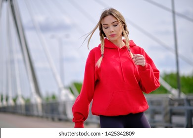 Young woman resting by city  river. Joging outfit.