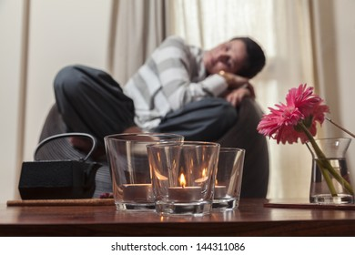 Young woman resting at the coach with focused foreground with candles / Relaxing moment