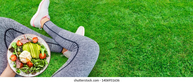 Young woman is resting and eating a healthy food after a workout. Fitness and healthy lifestyle concept.