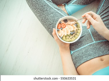 Young woman is resting and eating a healthy oatmeal after a workout. Fitness and healthy lifestyle concept.