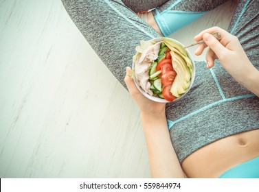 Young woman is resting and eating a healthy salad after a workout. Fitness and healthy lifestyle concept.