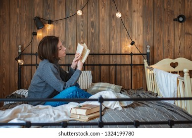 young woman is resting at home on the bed and reading a book near the cot. Mom is resting. quiet hour wooden background garland bulbs
