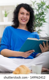 young woman resting at home, reading a book