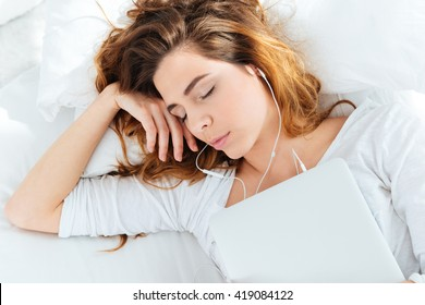 Young woman resting with laptop and headphones on the bed at home