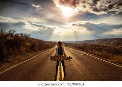 young woman resting with longboard on a hill overlooking the city below in the valley during sunrise or sunset with a toned vintage retro instagram filter