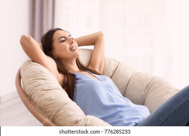 Young woman resting in lounge chair at home