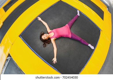 Young woman is resting and lying on a trampoline after doing some exercise session, concept of hard workout