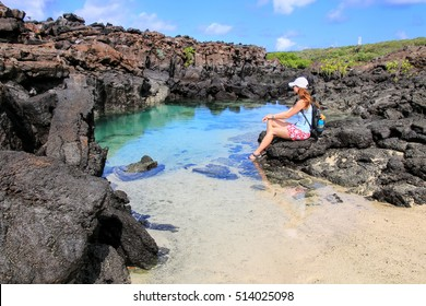 Young woman resting near small lagoon with clear water, Genovesa Island in Galapagos National Park, Ecuador