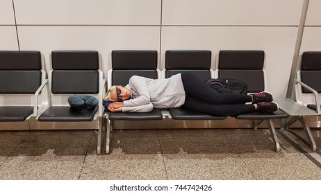 Young woman resting on the airport terminal between two flights