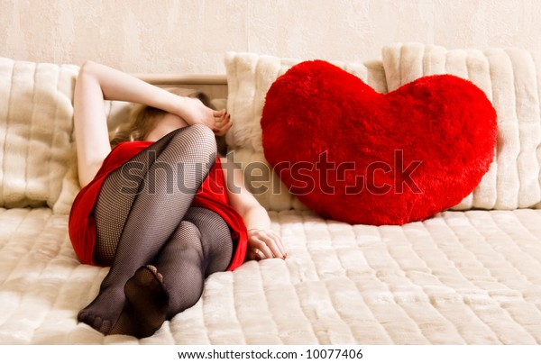 Young woman resting on a bed and heart shaped pillow. Concept image about unrequited love.