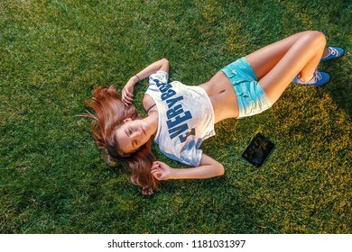 Young woman resting on grass with tablet computer lying near and long ginger hair spreaded about head