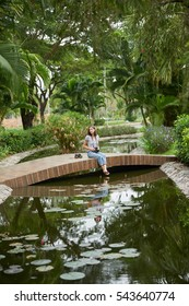 Young woman resting on little bridge over river in park