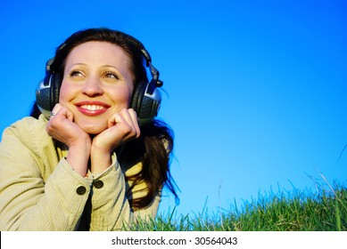 Young woman resting on meadow with headphones