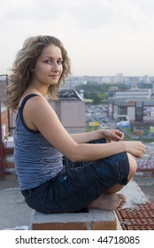 Young woman resting on residental building roof