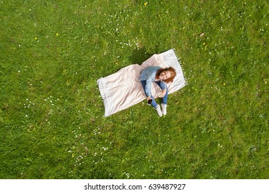 Young woman resting on a rug on grass looking up at the camera way above her as she enjoys the spring sunshine with copy space