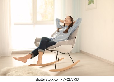 Young woman resting in rocking chair at home