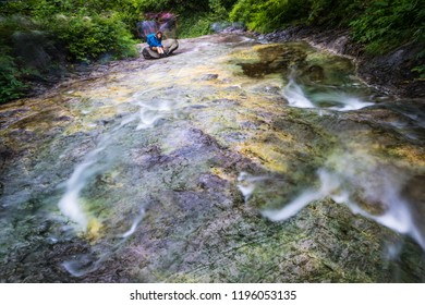A young woman rests along the natural hot spring stream of Kamuiwakka Falls in Shiretoko National Park and World Heritage Site, Hokkaido, Japan