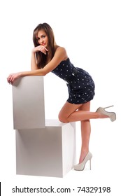 young woman rests her elbows on the white cube. Isolated background