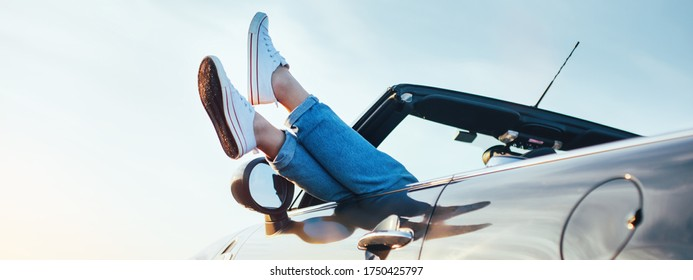 A young woman rests and pushes her sneakers out of the convertible to enjoy the view. Wide screen panoramic