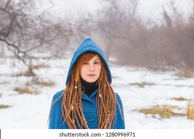 Young woman in retro blue coat walk in the foggy park in the winter times, snow and trees background,fantasy or fairy concept