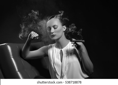 Young woman in retro chicago gangster style with cigar on a red chair over smoky background. Studio portrait. Black and white