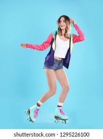 Young woman with retro roller skates on color background