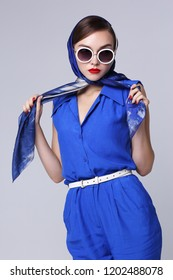 Young woman in retro style. Sunglasses and silk scarf, blue overalls. Sixties style fashion retro woman.