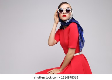 Young woman in retro style. Sunglasses and silk scarf. Sixties style fashion retro woman.