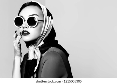 Young woman in retro style. Sunglasses and silk scarf. Sixties style fashion retro woman. Black and white image
