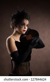 Young woman in retro style with vinyl records on a brown background