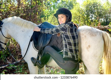 a young woman rider mounting a white horse