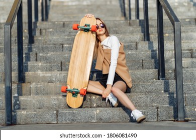 Young woman rides a longboard around the city.