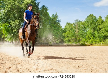 Young woman riding bay horse at sand racetrack